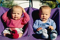 Infant twins sitting in a dual stroller getting ready to be taken for a walk on a sunny day.