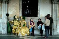Two people in costumes sitting with tourists, Venice, Veneto, Italy