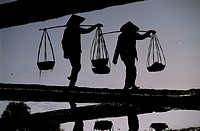 Silhouette of two people carrying basket at dusk, Vietnam