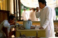 Side profile of a mature man drinking a cup of tea with another mature man eating food, Vietnam