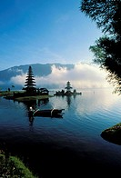 Indonesia, Bali, Ulu Danu temple at sunrise, canoe paddling on water NO MODEL RELEASE