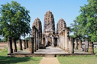 Thailand, Sukhothai Khmer Sanctuary ruins, view from front with trees and grass
