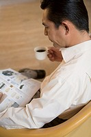 Man drinking coffee, reading a magazine