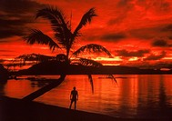Island sunset in South Pacific in Figi with man and palm tree along calm shore