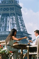 Couple having breakfast on Seine River houseboat in Paris with Eiffel Tower beyond