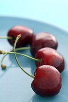 Red cherries on a blue plate