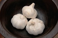 Garlic bulbs in black bowl