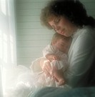 Mother holding her sleeping, infant daughter as she sits by the window.
