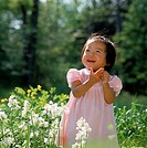 A smiling young Asian girl wearing a dress with pink stripes looking up to the sky while standing in a field of wildflowers.