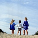 View from behind three young children, one girl and two boys, hold hands while standing at the crest of a sand dune.