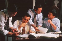 Group of Asian businessmen talking around a conference table.