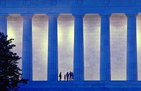 Several people stand between the columns of the Lincoln Memorial at dusk, Washington, DC.