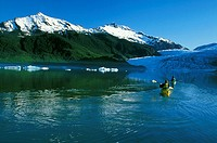 Two kayakers on Mendenhall Lake near Juneau, Alaska. Mendenhall Glacier and icebergs in the background.