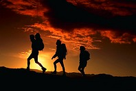 Sihouette of three hikers against sunrise in the summertime, Rocky Mountains, CO