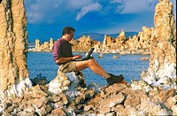 Man wearing shorts and using a laptop computer outside while sitting on a calcified rock formation along Mono Lake.