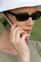 Young woman with sunglasses using a cellphone in a park