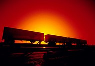 "Side view of ""piggy back"" trailers on rail cars with the sun setting in the background."