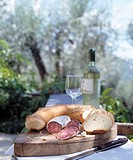 Mediterranean stillife: Bread, wine and salami, outdoors
