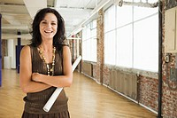 Woman Standing in Loft Holding Plans