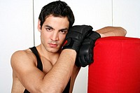 Young man leaning on punching bag
