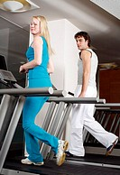 Young woman and man on treadmill