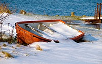 Small boat forgotten in all the snow in winter. Jutland Denmark