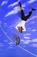 Businessman Unicycling Upside Down on High Wire