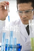 Male scientist wearing goggles, dropping blue liquids into test tubes with pipette, front view, differential focus