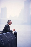 Businessman Leaning Against Railing