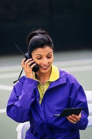 Woman with Cell Phone on Tennis Court