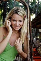 Beautiful blonde woman sat outside talking on the phone, shot in the morning in India