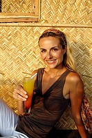 Portrait of beautiful blonde woman drinking a cocktail, shot in an Indian beach hut
