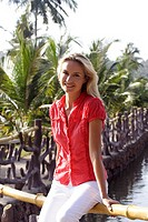 Portrait of beautiful blonde woman sat on a fence by a lagoon in India