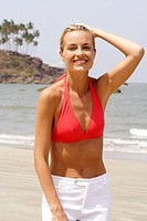 Portrait of beautiful blonde woman in red bikini top on a beach in India
