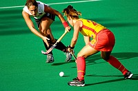 two field hockey female players fighting for the ball