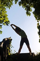 Silhouetted young woman exercising