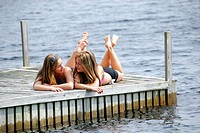 sisters 13 and 18 yrs laying on dock together