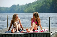 sisters 13 and 18 yrs sitting on dock laughing together