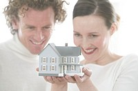 Couple Holding Model of House