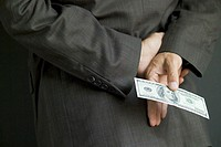 Businessman Holding $100 Bill Behind Back