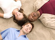 Friends Lying in Sand with Eyes Closed