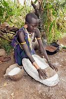 Surma woman grinding corn. Near Kibish. Ethiopia.