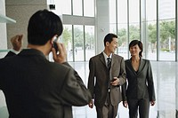 Businessman and businesswoman walking side by side, man on mobile phone in foreground