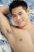 Young man lying down, smiling at camera