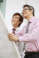 Two businessmen looking at blueprints, smiling