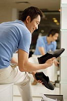 Man in shoe shop, looking at shoes