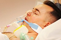 Intensive care patient  Side-view of the face of a male patient in the intensive care unit of a hospital  He is attached to a respirator to help him t...