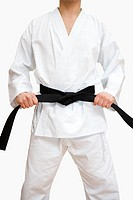Karate  Karate practitioner pulling on his black belt  Karate is a martial art originating from Okinawa in Japan  It is characterised by powerful kick...