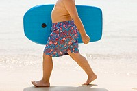 Holiday  Boy walking along a beach holding a body board