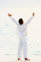 Man in White Raising Arms at Ocean
